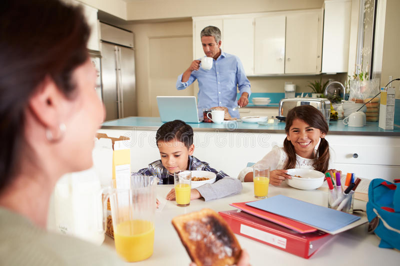 Hispanic Family Eating Breakfast At Home Before School. With Daughter Smiling At Mother stock image