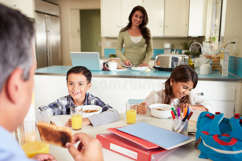 Hispanic Family Eating Breakfast At Home Before School. Sitting At Kitchen Table Smiling royalty free stock images