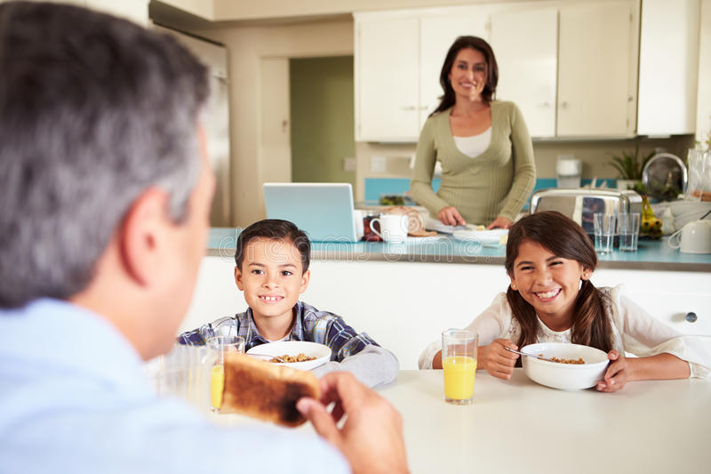 Hispanic Family Eating Breakfast At Home Together. Looking At Father Smiling royalty free stock photography