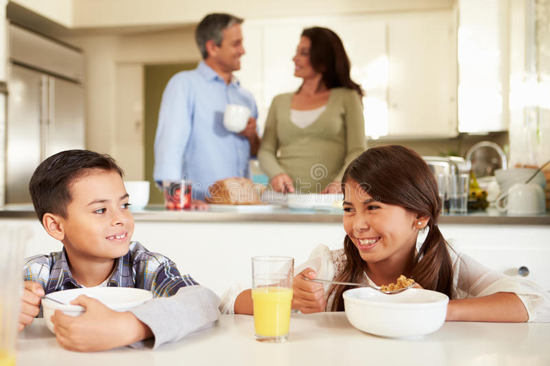 Hispanic Family Eating Breakfast At Home Together. Smiling At Each Other royalty free stock photos