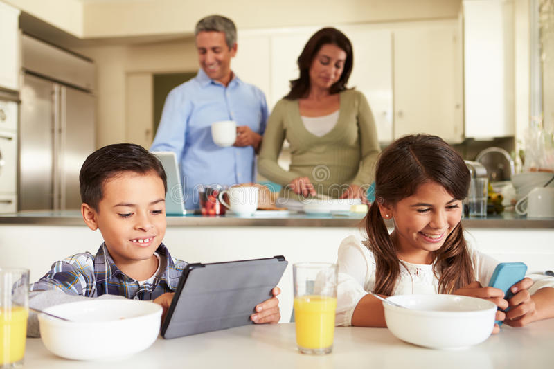 Hispanic Family Eating Breakfast Using Digital Devices. With Children Sitting At Table Smiling stock image