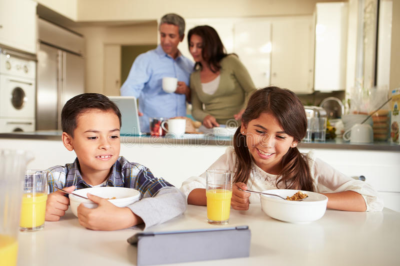 Hispanic Family Eating Breakfast Using Digital Devices. In Kitchen stock image
