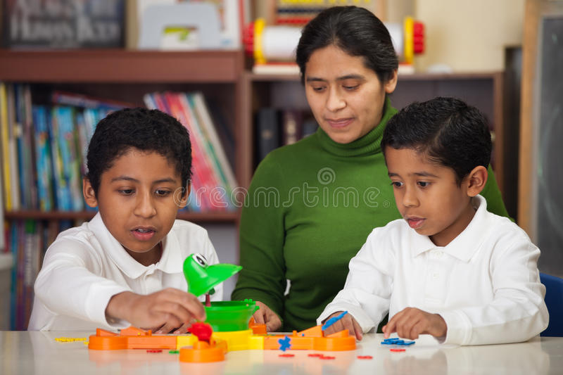 Hispanic Family Playing Mr. Frog. In Classroom stock photo