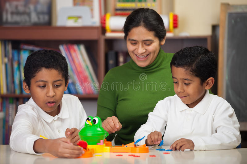 Hispanic Family Playing Mr. Frog. In Home-School Setting royalty free stock images