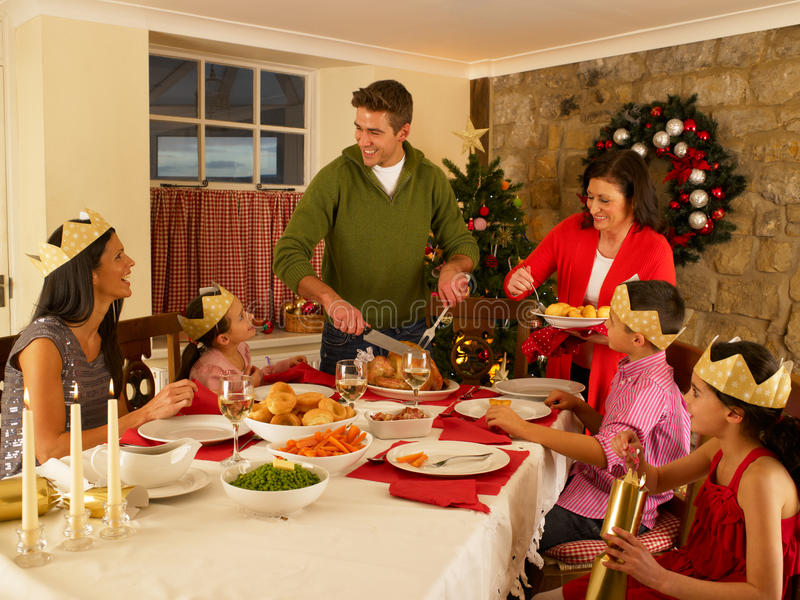Download Hispanic Family Serving Christmas Dinner Stock Photo