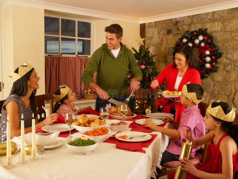 Download Hispanic Family Serving Christmas Dinner Stock Photo