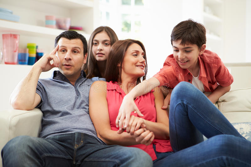 Hispanic Family On Sofa Watching TV Together