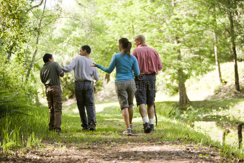 Hispanic family walking along trail in park stock image