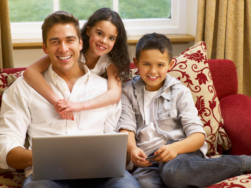 Hispanic father and children shopping online. Smiling at camera royalty free stock images