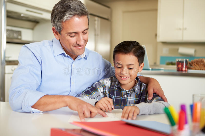 Hispanic Father Helping Son With Homework At Table. With Arm Around Shoulder royalty free stock images