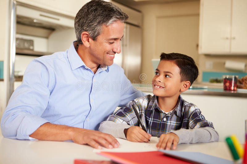 Hispanic Father Helping Son With Homework At Table. In Kitchen Sitting Down Smiling At Each Other stock photo