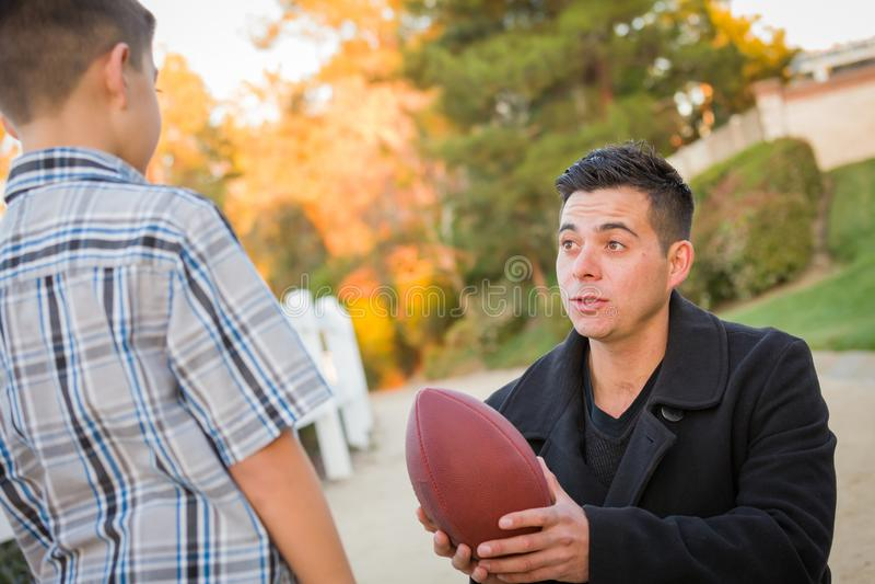 Hispanic Father Holding Football Teaching Young Boy stock photos