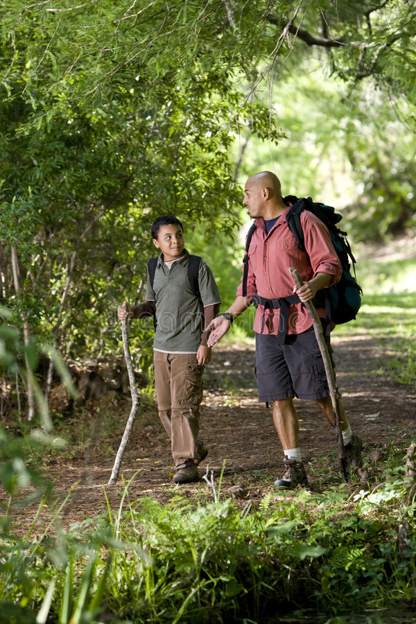 Download Hispanic Father And Son Hiking On Trail In Woods Stock Photo