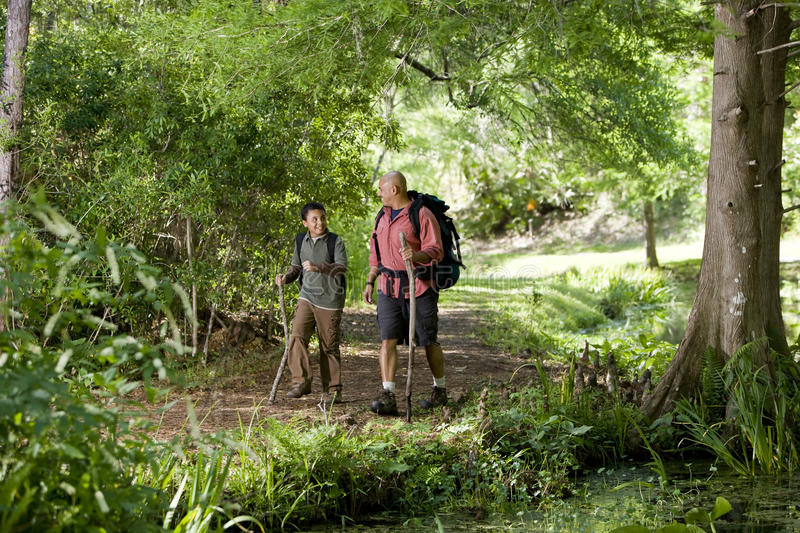 Hispanic father and son hiking on trail in woods royalty free stock photos
