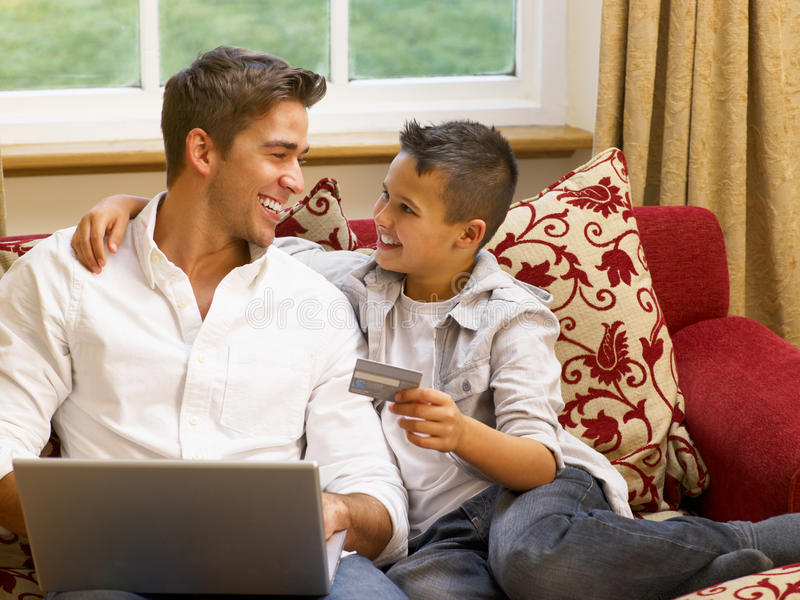 Hispanic father and son shopping online. At home stock photo