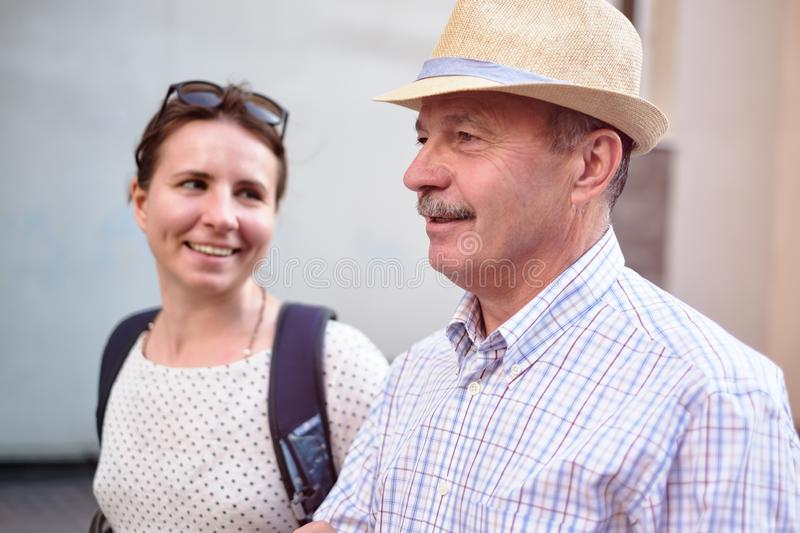 Hispanic father in summer hat and daughter walking outdoor together. Happy mature men walking with young woman. Hispanic father in summer hat and daughter royalty free stock images