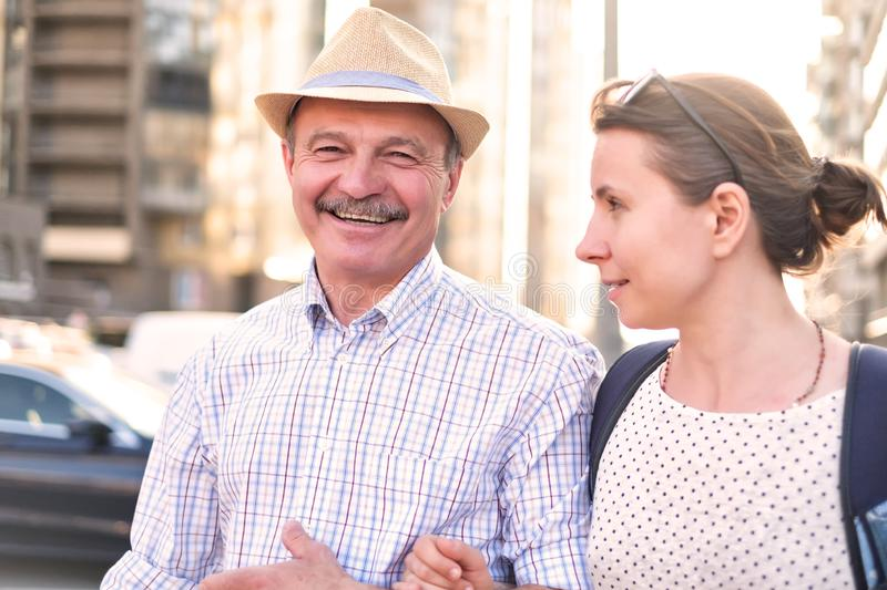 Hispanic father in summer hat and daughter walking outdoor together. Happy mature man walking with young woman. Hispanic father in summer hat and daughter stock photography