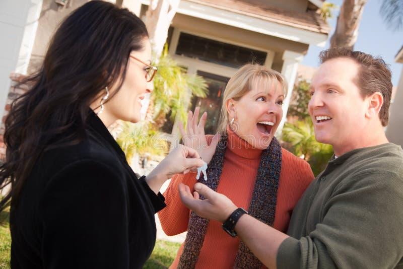 Hispanic Female Real Estate Agent Handing Keys to stock photography