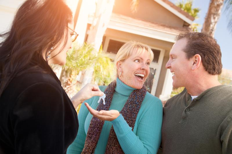 Hispanic Female Real Estate Agent Handing Over New House Keys to Happy Couple In Front of House royalty free stock image