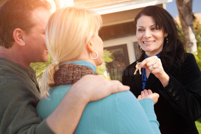 Hispanic Female Real Estate Agent Handing Over New House Keys to Happy Couple In Front of House. Hispanic Female Real Estate Agent Handing Over New House Keys to royalty free stock photography