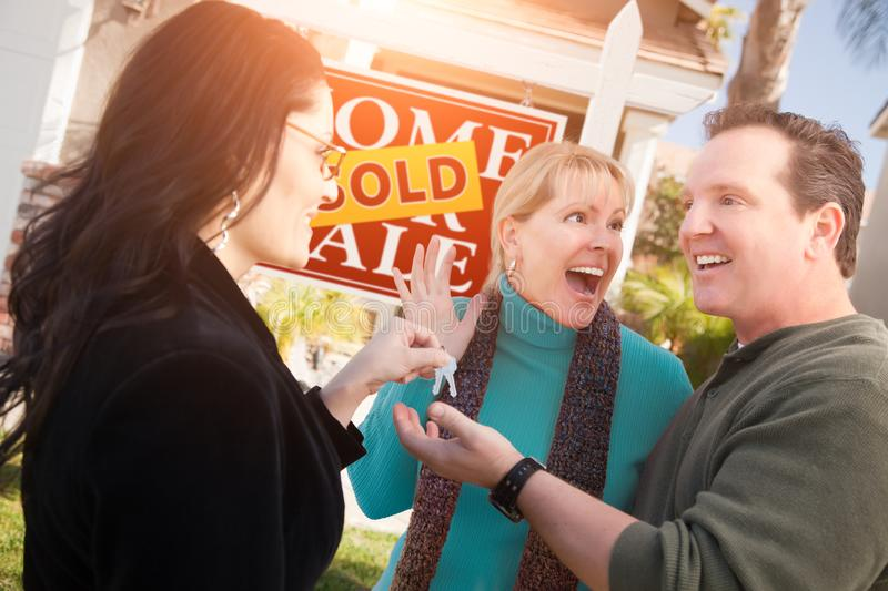Hispanic Female Real Estate Agent Handing Over New House Keys to Happy Couple In Front of Sold For Sale Real Estate Sign.  royalty free stock photography