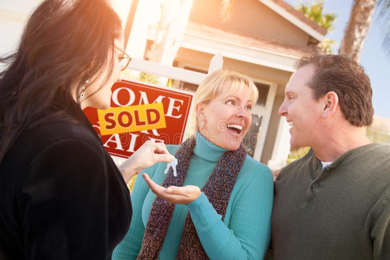 Hispanic Female Real Estate Agent Handing Over New House Keys to Happy Couple In Front of Sold For Sale Real Estate Sign. Hispanic Female Real Estate Agent stock photography