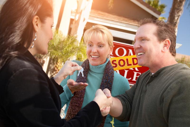 Hispanic Female Real Estate Agent Handing Over New House Keys to Happy Couple In Front of Sold For Sale Real Estate Sign.  royalty free stock photo