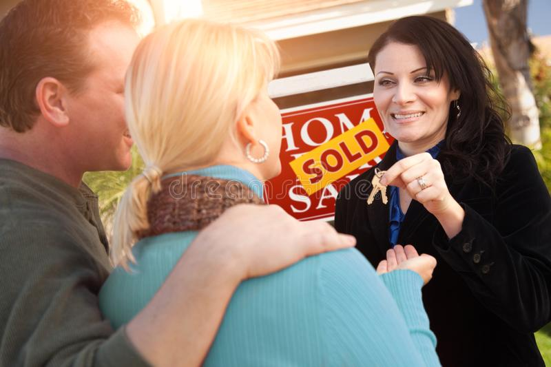 Hispanic Female Real Estate Agent Handing Over New House Keys to Happy Couple In Front of Sold For Sale Real Estate Sign.  stock photography