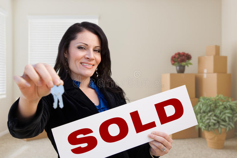 Hispanic Female Real Estate Agent with Sold Sign and Keys in Room with Moving Boxes. royalty free stock image
