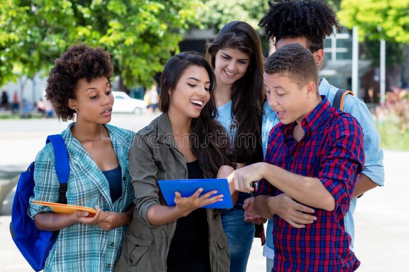 Hispanic female student learning with group of latin and african american young adults royalty free stock images