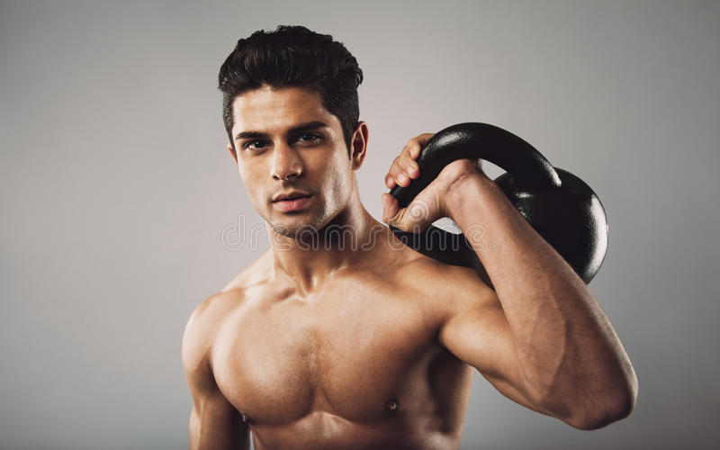 Hispanic fitness male model holding kettle bell. Portrait of hispanic fitness male model holding kettle bell on grey background. Shirtless young doing crossfit stock images