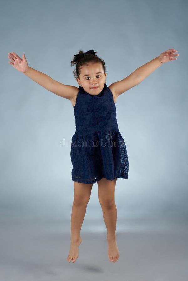 Hispanic girl jump in studio stock photography