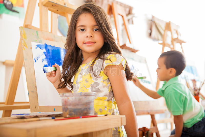 Hispanic girl painting in art class. Portrait of a gorgeous little Hispanic girl holding a paintbrush and working on a painting for art class stock photo