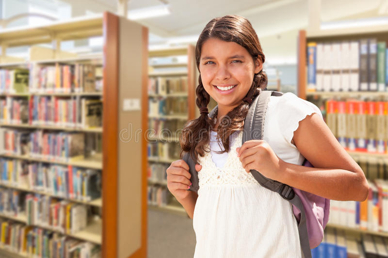 Hispanic Girl Student Walking in Library. Happy Hispanic Girl Student Wearing Backpack Walking in the Library stock photo