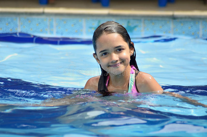 Hispanic Girl Swimming and Playing. Child plays and relaxes in a swimming pool stock image