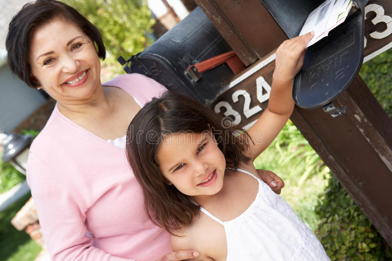 Hispanic Grandmother And Granddaughter Checking Mailbox royalty free stock image