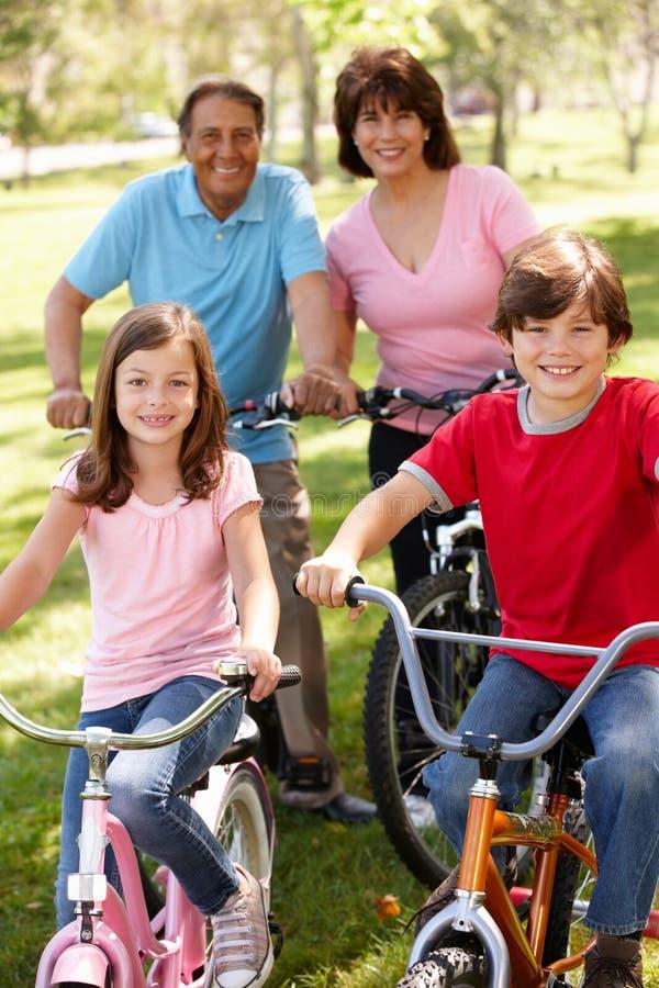 Hispanic grandparents with grandchildren on bikes royalty free stock photo