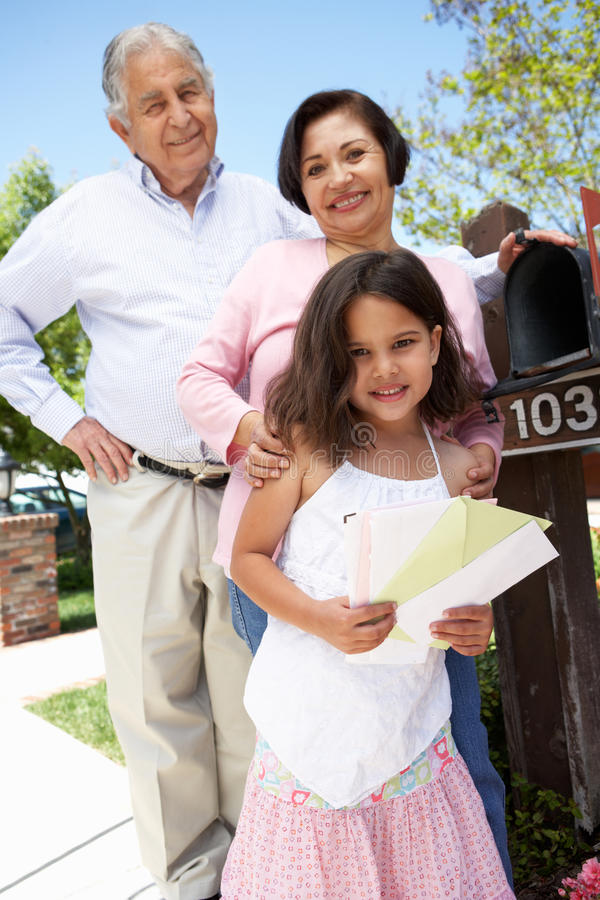 Hispanic Grandparents And Granddaughter Checking Mailbox royalty free stock images