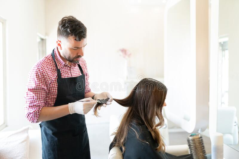 Hispanic Hairstylist Dyeing Hair Of Customer. Male hairdresser applying dye on hair of young women at beauty studio stock image
