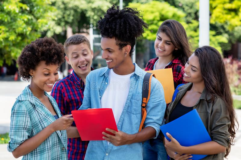Hispanic hipster student learning with group of latin and african american young adults. Outdoor at campus of university royalty free stock image