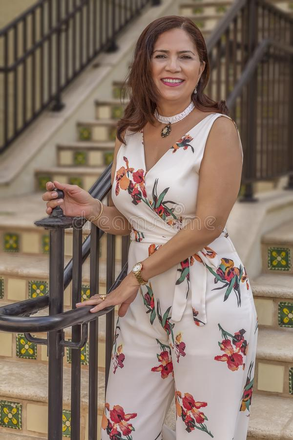 A sophisticated latin mature woman stops at the bottom of the stairs for a photo op stock image