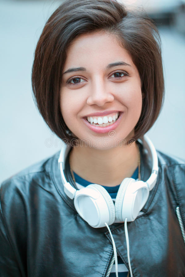 Hispanic latin girl woman short black hair in leather jacket with headphones, outside in evening night city street stock images