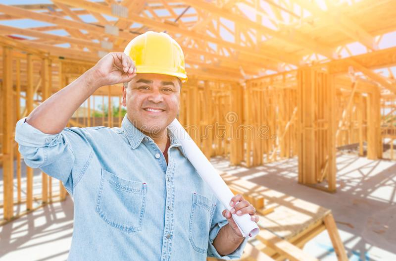 Hispanic Male Contractor with Blueprint Plans Wearing Hard Hat At Construction Site.  royalty free stock photography