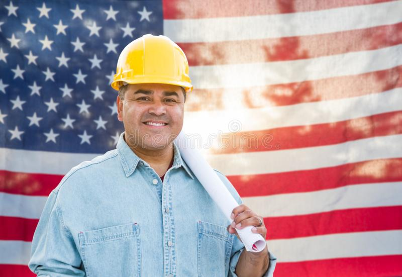Hispanic Male Contractor with Blueprint Plans Wearing Hard Hat In Front of American Flag stock images