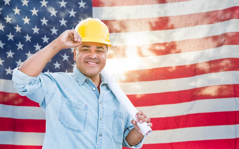 Hispanic Male Contractor with Blueprint Plans Wearing Hard Hat In Front of American Flag.  royalty free stock images