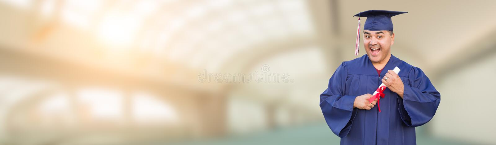 Hispanic Male With Diploma Wearing Graduation Cap and Gown On Campus Banner.  royalty free stock photos