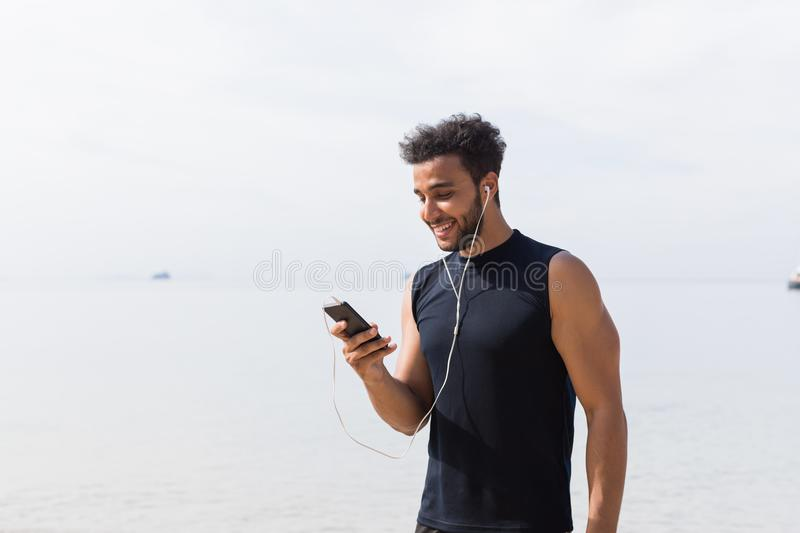 Hispanic Male Runner Using Cell Smart Phone On Beach While Jogging On Seaside Man Young Happy Smiling Latin Sport. Healthy Lifestyle Concept royalty free stock photos