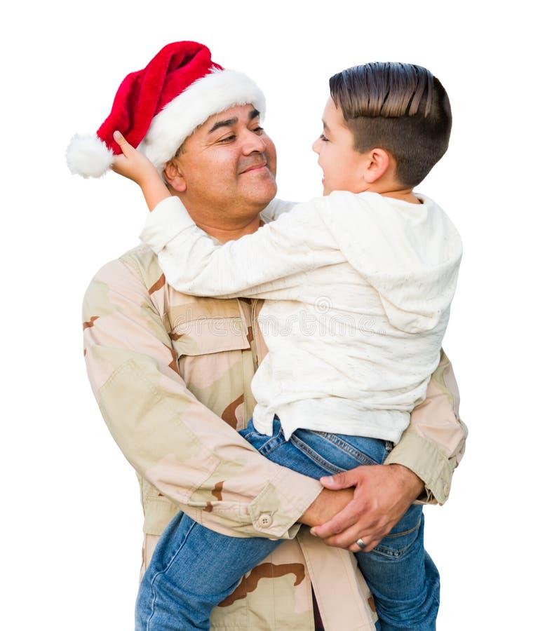 Hispanic Male Soldaat Wearing Santa Cap Holding Mixed Race Son, geïsoleerd op een witte achtergrond royalty-vrije stock foto's