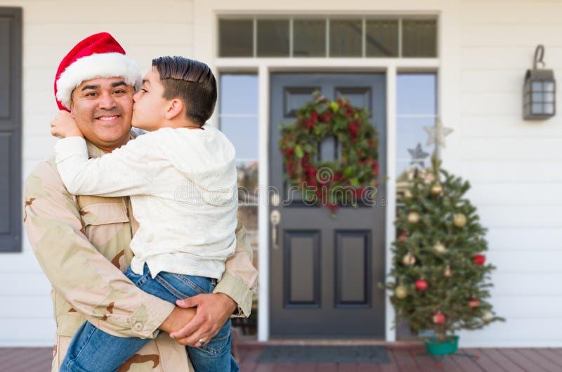 Hispanic Male Soldaat Wearing Santa Cap Holding Mixed Race Son voor House royalty-vrije stock afbeeldingen