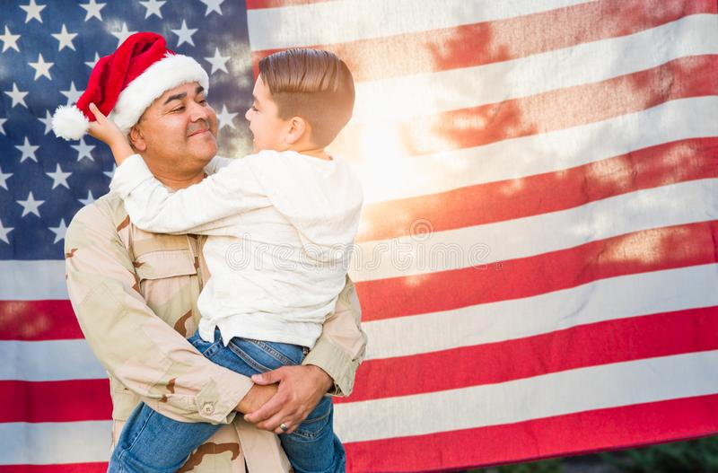 Hispanic Male Soldier Wearing Santa Cap Near American Flag. Hispanic Male Soldier Wearing Santa Cap Holding Mixed Race Son In Front of American Flag stock images